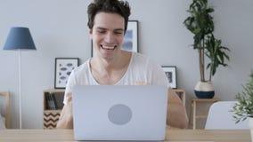 Творческий человек празднуя успешные результаты на работе, компьтер-книжке акции видеоматериалы