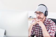 Творческий человек с наушниками слушая музыку на его компьютере стоковые фотографии rf
