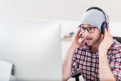 Творческий человек с наушниками слушая музыку на его компьютере стоковые изображения