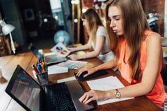 2 творческих женских график-дизайнера работая на компьтер-книжке на офисе Стоковое фото RF