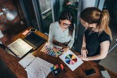 2 творческих женских дизайнера выбирая цвета работая с палитрой цвета в офисе Стоковая Фотография RF