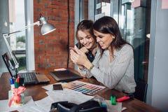 2 творческих женских дизайнера выбирая цвета работая с палитрой цвета в офисе Стоковые Фото