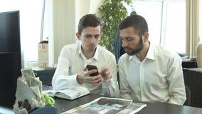 2 творческих молодые люди в офисе Посмотрите телефон акции видеоматериалы