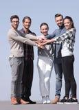 Творческое молодые люди сжимано их рукам совместно стоковые фото