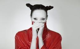 Творческое очарование Молодая женщина в модном красном длинном плаще лака Сумасшедший макияж моды стоковая фотография