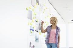 Творческое сочинительство коммерсантки на липкой бумаге в офисе Стоковое Изображение