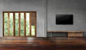 ТВ на бетонной стене с высокорослыми окнами в старых деревянных полах опорожняет комнату Стоковая Фотография