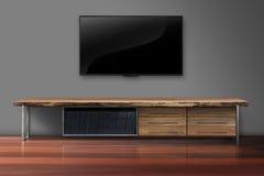 ТВ приведенное на серой стене цвета с комнатой деревянного стола живущей Стоковая Фотография