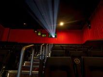 Театр комнаты фильма серебряный экранируя со светом репроектора на и посадочными местами и лестницами на сочных занавесах красног стоковая фотография rf