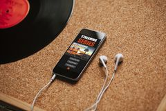 Текл серия app в экране мобильного телефона, близко к белым наушникам на коричневой таблице Стоковые Фотографии RF