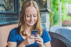Текстовое сообщение женщины печатая на умном телефоне в кафе Молодая женщина сидя на таблице с кофе используя мобильный телефон Стоковые Изображения RF