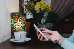 Текстовое сообщение женщины печатая на умном телефоне в кафе на деревянном Стоковая Фотография