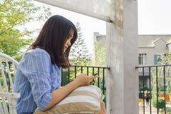 Текстовое сообщение женщины печатая на умном телефоне в кафе Подрезанное изображение молодой женщины сидя на таблице с кофе Стоковая Фотография RF