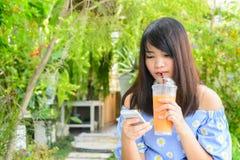 Текстовое сообщение женщины печатая на умном телефоне в кафе Подрезанное изображение молодой женщины сидя на таблице с кофе испол Стоковая Фотография