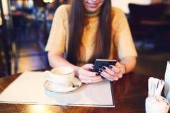 Текстовое сообщение женщины печатая на умном телефоне в кафе Подрезанное изображение молодой женщины сидя на таблице с кофе испол Стоковое Изображение