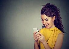 Текстовое сообщение женщины печатая на smartphone имея приятный переговор стоковое изображение rf