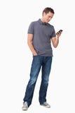 Текстовое сообщение молодого человека печатая на машинке на его мобильном телефоне стоковые фото
