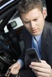 Текстовое сообщение чтения бизнесмена на его сотовом телефоне Стоковые Фотографии RF