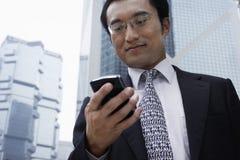 Текстовое сообщение чтения бизнесмена на сотовом телефоне Стоковые Изображения
