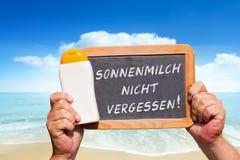 Текстовое сообщение - nicht Sonnenmilch vergessen на шифере Стоковые Фото