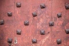 Текстура античных квадратных ногтей на старой традиционной красной двери Стоковые Изображения RF