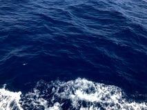 Текстура бурля голубой морской воды с волнами, пузырями, пеной, трассировками после быстрой плавая тележки, шлюпки стоковое фото rf