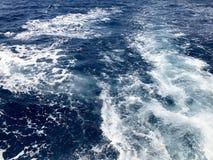 Текстура бурля голубой соленой воды моря с волнами, расслоины, пузыри, пена, следует, брызгает после быстрой плавая тележки, bo стоковое изображение