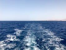 Текстура бурля голубой соленой воды моря с волнами, расслоины, пузыри, пена после стремительно плавая автомобиля, шлюпки против стоковая фотография rf