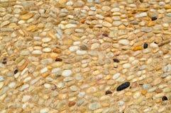 Текстура каменной стены, дорог от малого кругом и овальных камней с песком с швами естественного старого желтого черного коричнев стоковые фотографии rf