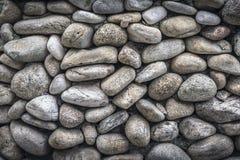 Текстура каменной стены, положенная из больших округленных валунов, приспособлена плотно друг к другу Стоковые Фото