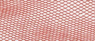 Текстура - красная пластичная сетка для упаковки, транспорта и продажи овощей Стоковое фото RF