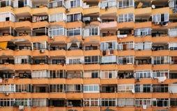 Текстура многоэтажной стены дома с балконами и окнами Стоковые Изображения RF