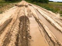 Текстура пакостной плохой грязной улицы грязной улицы с лужицами и грязи засыхания глины с отказами и колейностями Внедорожный зе стоковая фотография