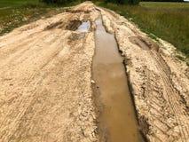 Текстура пакостной плохой грязной улицы грязной улицы с лужицами и грязи засыхания глины с отказами и колейностями Внедорожный зе стоковое фото