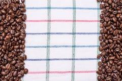 Текстура покрашенного полотенца, полотенца клетчатого типа, на котором лежат некоторое количество коричневых кофейных зерен Взгля Стоковые Изображения