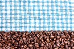 Текстура покрашенного полотенца, полотенца клетчатого типа, на котором лежат некоторое количество коричневых кофейных зерен Взгля Стоковое Фото