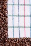 Текстура покрашенного полотенца, полотенца клетчатого типа, на котором лежат некоторое количество коричневых кофейных зерен Взгля Стоковое Изображение