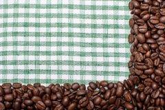 Текстура покрашенного полотенца, полотенца клетчатого типа, на котором лежат некоторое количество коричневых кофейных зерен Взгля Стоковые Фото
