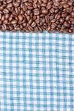 Текстура покрашенного полотенца, полотенца клетчатого типа, на котором лежат некоторое количество коричневых кофейных зерен Взгля Стоковое фото RF