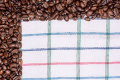 Текстура покрашенного полотенца, полотенца клетчатого типа, на котором лежат некоторое количество коричневых кофейных зерен Взгля Стоковые Фотографии RF