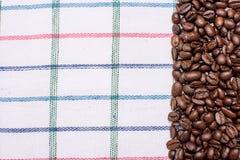 Текстура покрашенного полотенца, полотенца клетчатого типа, на котором лежат некоторое количество коричневых кофейных зерен Взгля Стоковая Фотография