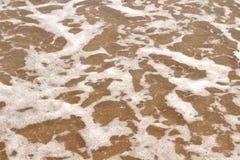 Текстура предпосылки песка, пены и воды Стоковые Изображения