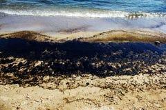 Текстура расслоины сырой нефти на пляже от аварии нефтяного пятна, заливе песка Kosmas ажио, Афинах, Греции, 14-ое сентября 2017 Стоковое фото RF