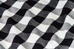 Текстура скомканной рубашки, белая черная ткань для предпосылки стоковые изображения