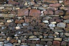 Текстура, стена предпосылки клала естественные камни различных размеров и цветов Стоковая Фотография