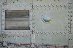 Текстура стены танка, сделанной из металла и усиленной с множеством болтов и заклепок Изображения заволакивания  стоковая фотография