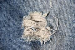 Текстура ткани джинсовой ткани сломанная джинсами Стоковая Фотография RF