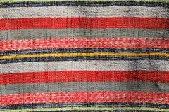 Текстура handmade ковра произвела на ручном станке, картине различных красных, белых, черных и желтых вертикальных линий Стоковые Фото