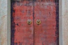 Текстурированные красные ворота металла с knockers двери китайского льва главными стоковое изображение