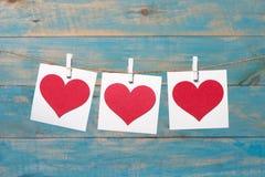 Текстурированные сердца вися на голубой деревянной предпосылке Стоковые Фото